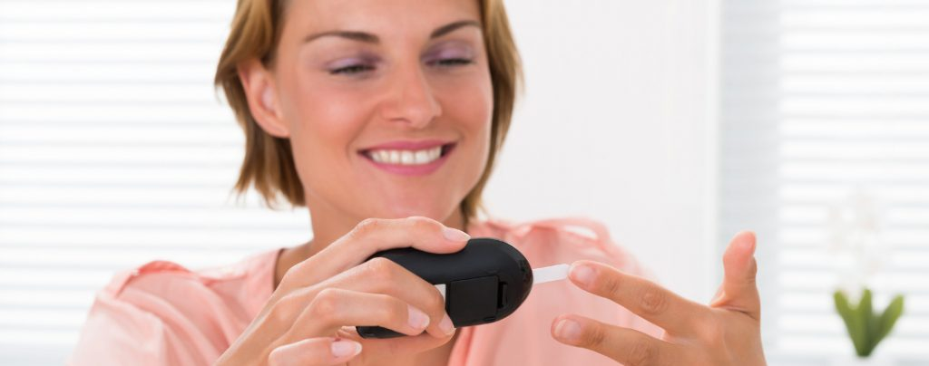 smiling woman checking blood sugar